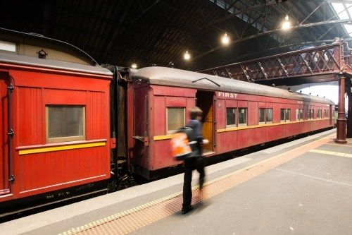 Conductor walking past a heritage carriage on a platform