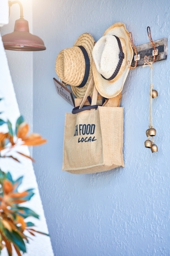 Hessian shopping bag and hats hanging on wall