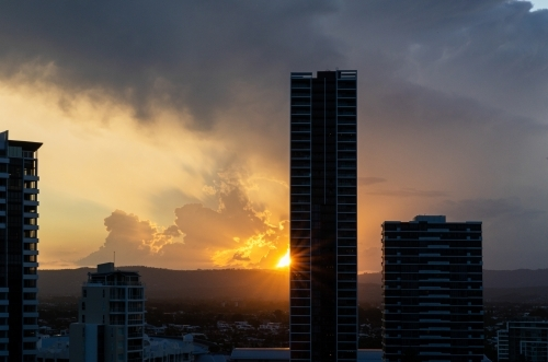 high rise buildings silhouetted against setting sun under stormy sky