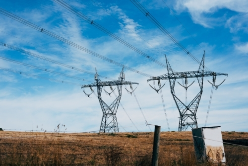 High voltage power transmission tower on blue sky background,  electricity distribution.