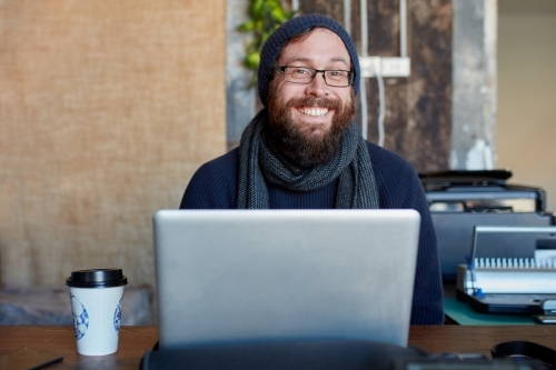 Hipster man with beard smiling at outdoor work table with a laptop