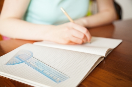 Girl writing in blank graph paper school book