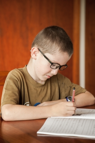 Young boy writing in his school work book with a pencil