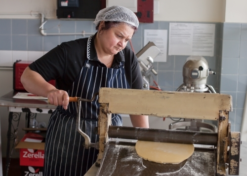 Hospitality worker running dough through a pastry roller