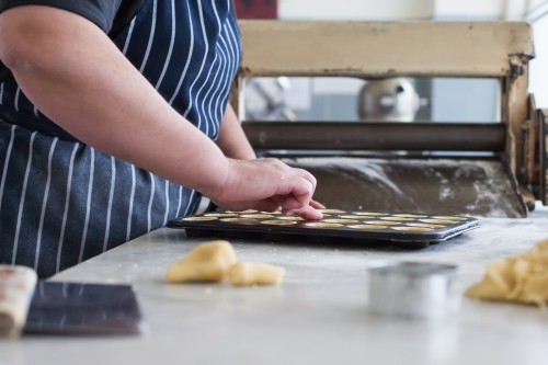 Hospitality worker working pastry into a baking tray