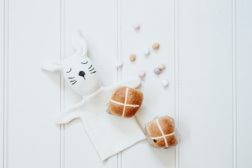 Hot cross buns, mini easter eggs and bunny rabbit on white background