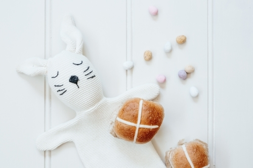 Hot cross buns with mini easter eggs and bunny rabbit puppet on white background