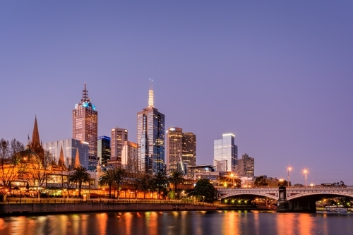 Illuminated Melbourne City skyline by Princes Bridge Over Yarra River Against Clear Sky