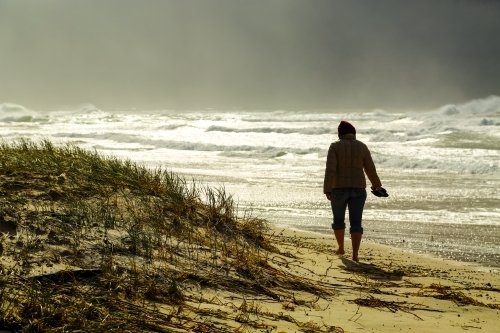 A lady in her mid thirties braves a storm as she strolls along a beach at Iluka, NSW