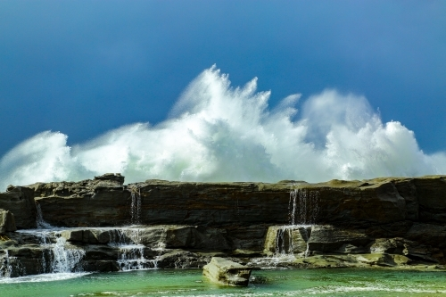 A large swell smashes against a rocky headland under a stormy sky in Iluka, New South Wales