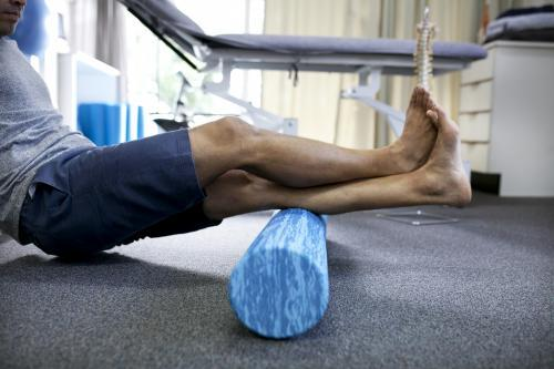 Detail shot of male patient using a foam roller in a physio studio