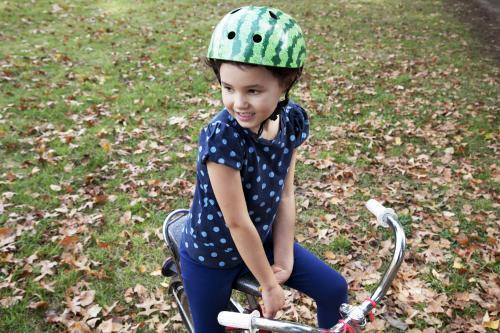 Young girl wearing helmet and sitting on bike