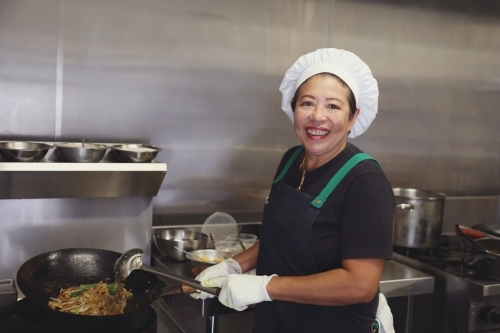 Asian female chef in commercial kitchen