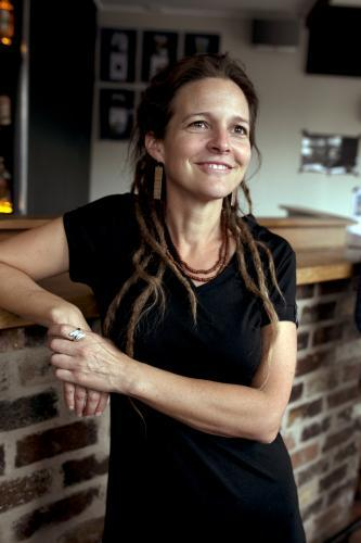 Smiling woman with dreadlocks resting against bar