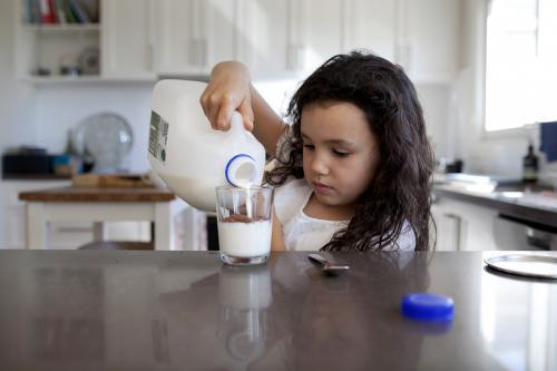 Young girl pouring milk into a glass