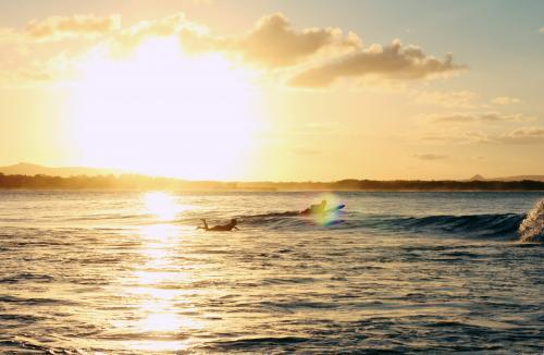Surfers Paddling at Sunset