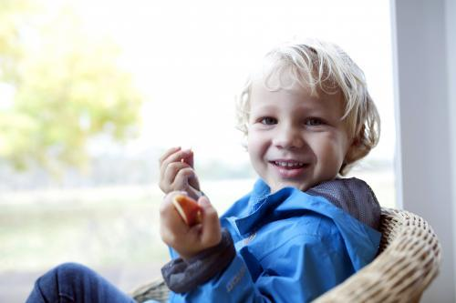 Smiling young boy wearing a blue jacket eating pieces of apple
