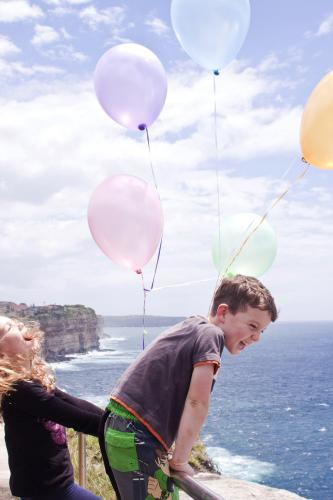 Two young kids with balloons by the ocean