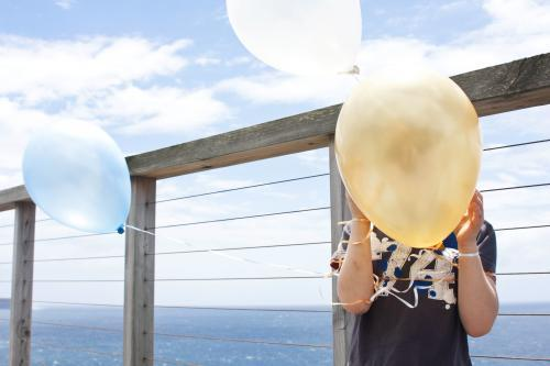 Boy holding balloons in his face by the sea