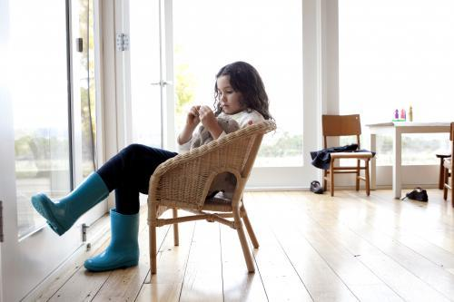 Girl wearing blue gumboots sitting inside on a wicker chair
