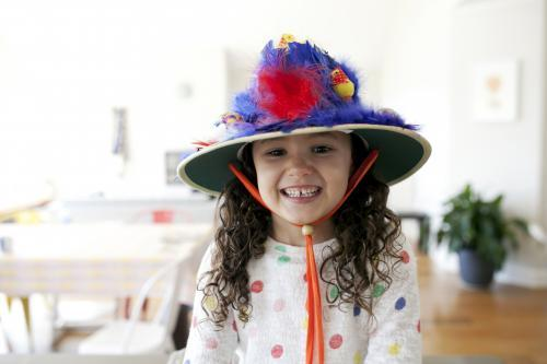 Smiling young girl wearing hand made Easter hat