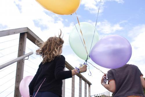 Boy and girl looking away into the wind holding balloons