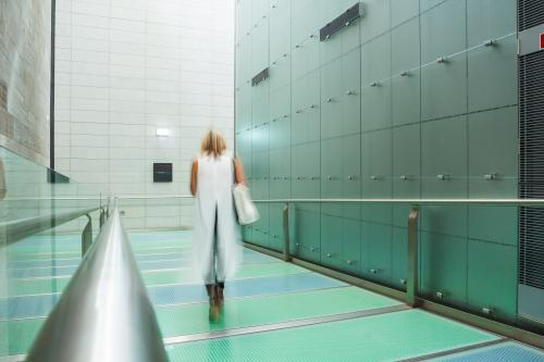 A lady walking through a gallery corridor