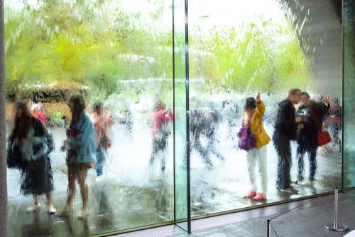 Looking through a glass water wall at a group of tourists