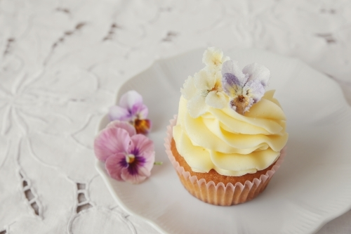 Yellow cupcakes with sugared edible flowers on vintage plate
