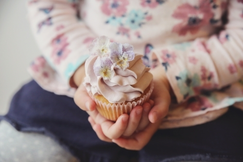 Childs hands holding purple flower cupcake