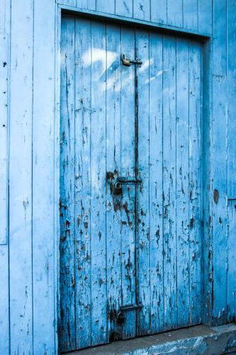 Locked and bolted old blue wooden door with paint peeling off