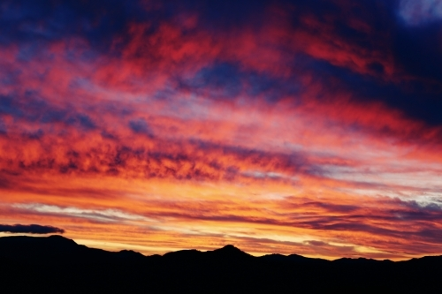 Brightly coloured sunset above mountains