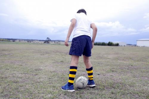 Boy standing over a football in a rural paddock