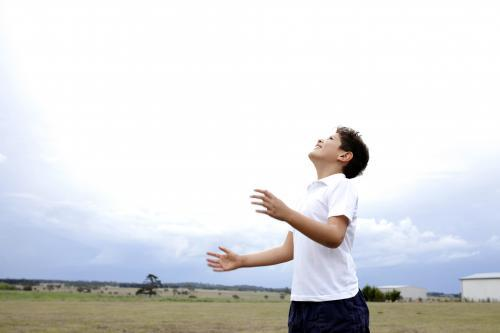Boy throwing ball up into air, looking up at sky