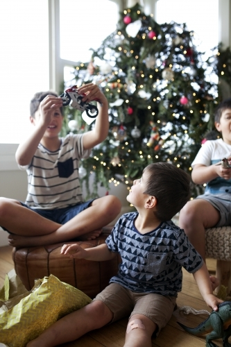 Three young boys opening christmas presents