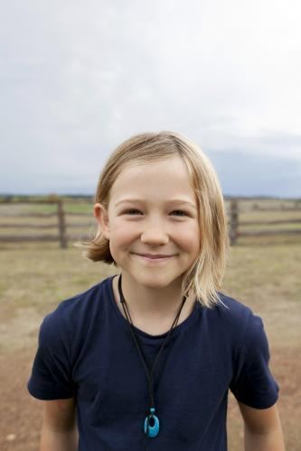 Portrait of a smiling blonde girl standing outside on farm