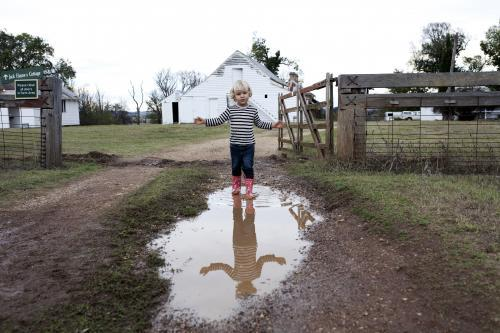Young boy wearing gumboots walking through muddy puddle