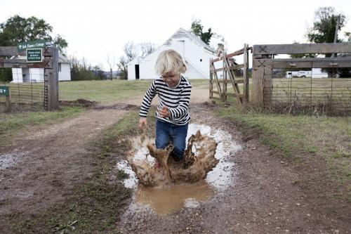 Young boy splashing in muddy puddle on the farm
