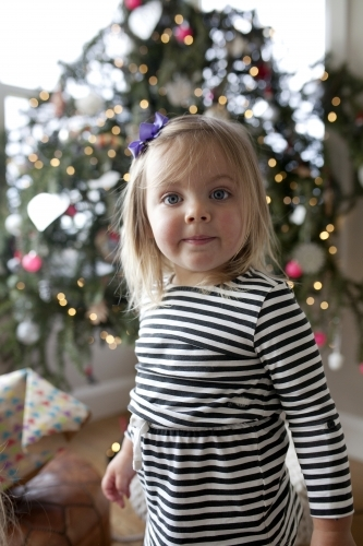 Young girl standing in front of Christmas tree
