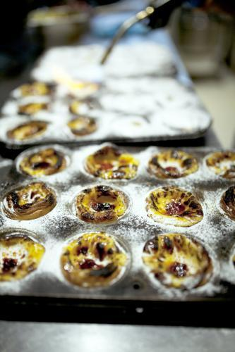 Using blow torch to caramelise freshly made Portugese tarts in tin at bakery cafe