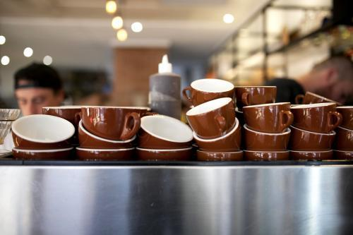 Brown coffee cups stacked on coffee machine at cafe