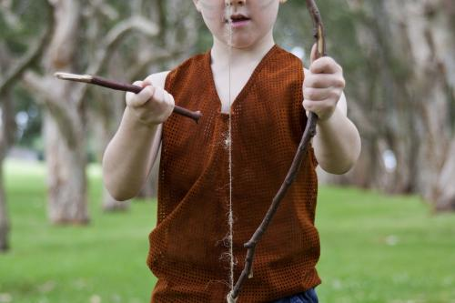 Little boy playing with homemade bow and arrow