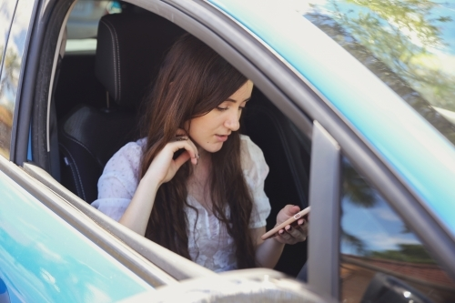 Teenage girl using mobile phone, waiting in the car