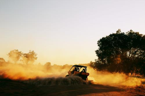 A quad bike doing a burnout in dust.