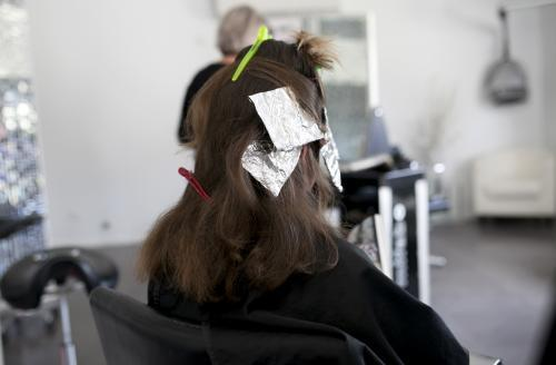 Woman from behind sitting with foils in her hair at hairdressers