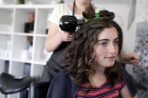 Young woman at hairdressers having hair styled