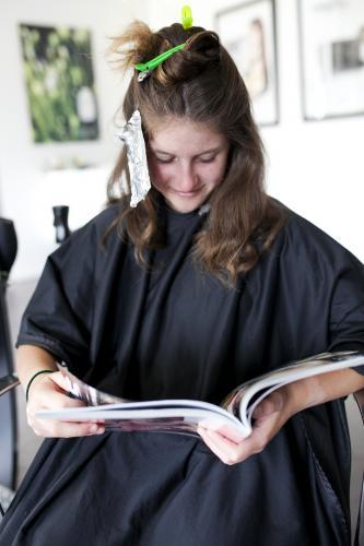 Young woman reading magazine at hairdressers with foils in hair