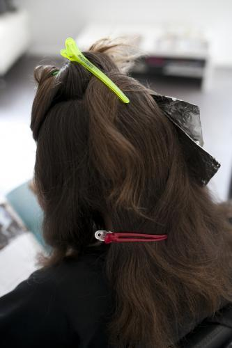 Woman at hairdressing salon from behind with hair clipped back