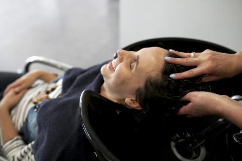 Woman smiling while having hair washed at hairdressing salon