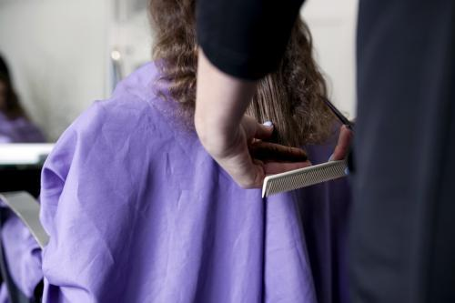 Young girl having hair cut from behind